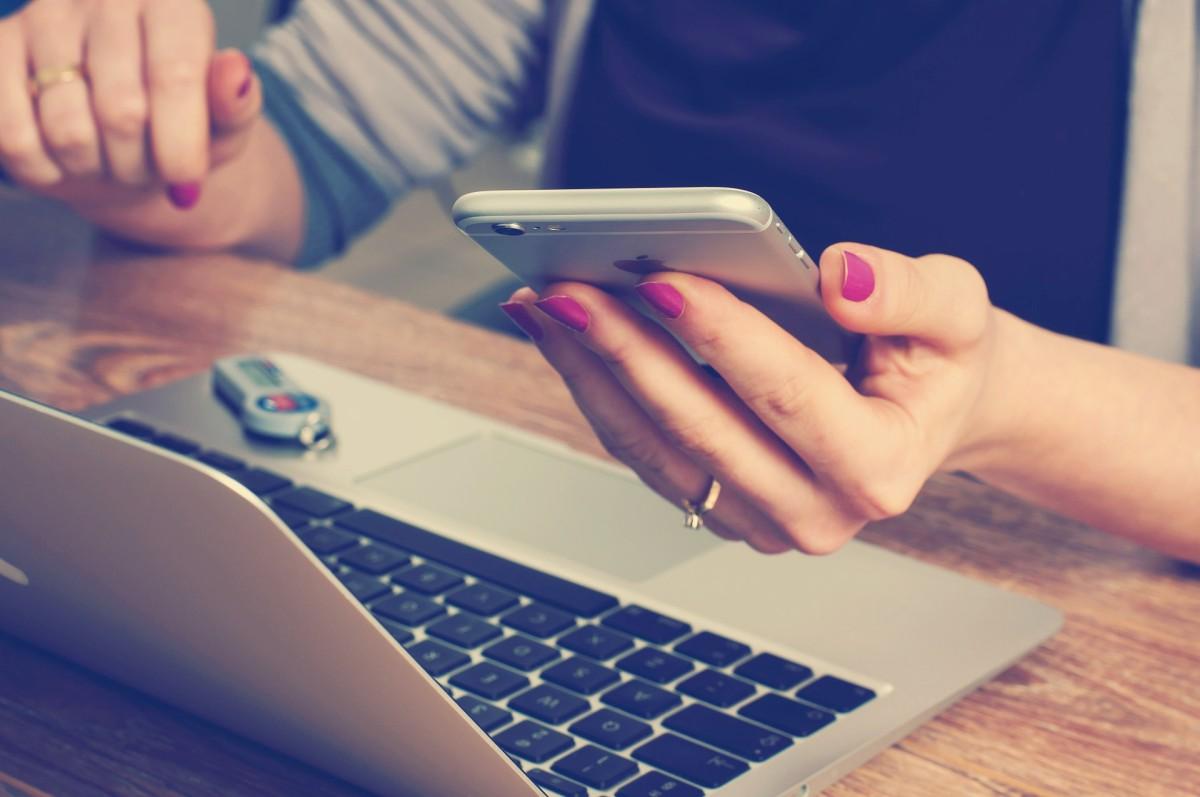 Femme au bureau, devant son ordinateur avec son téléphone dans la main.