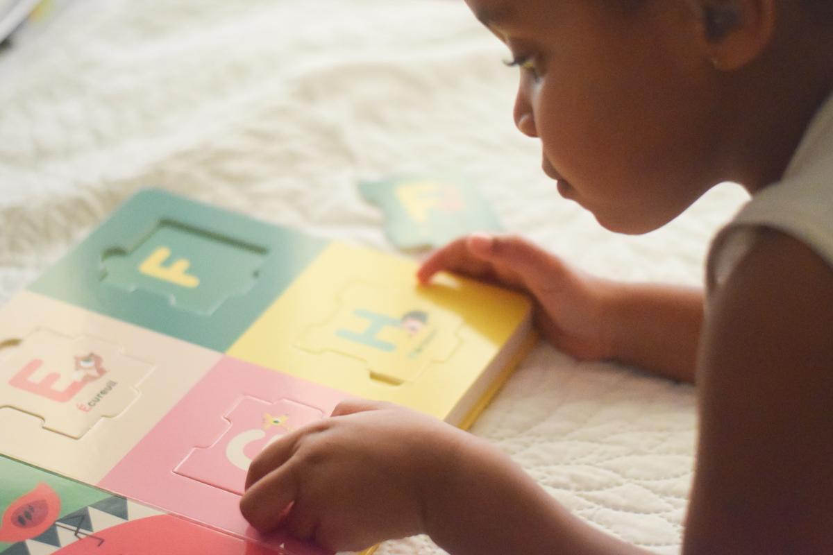 Main en train de détacher une pièce de l'abécédaire puzzle de chez Nathan