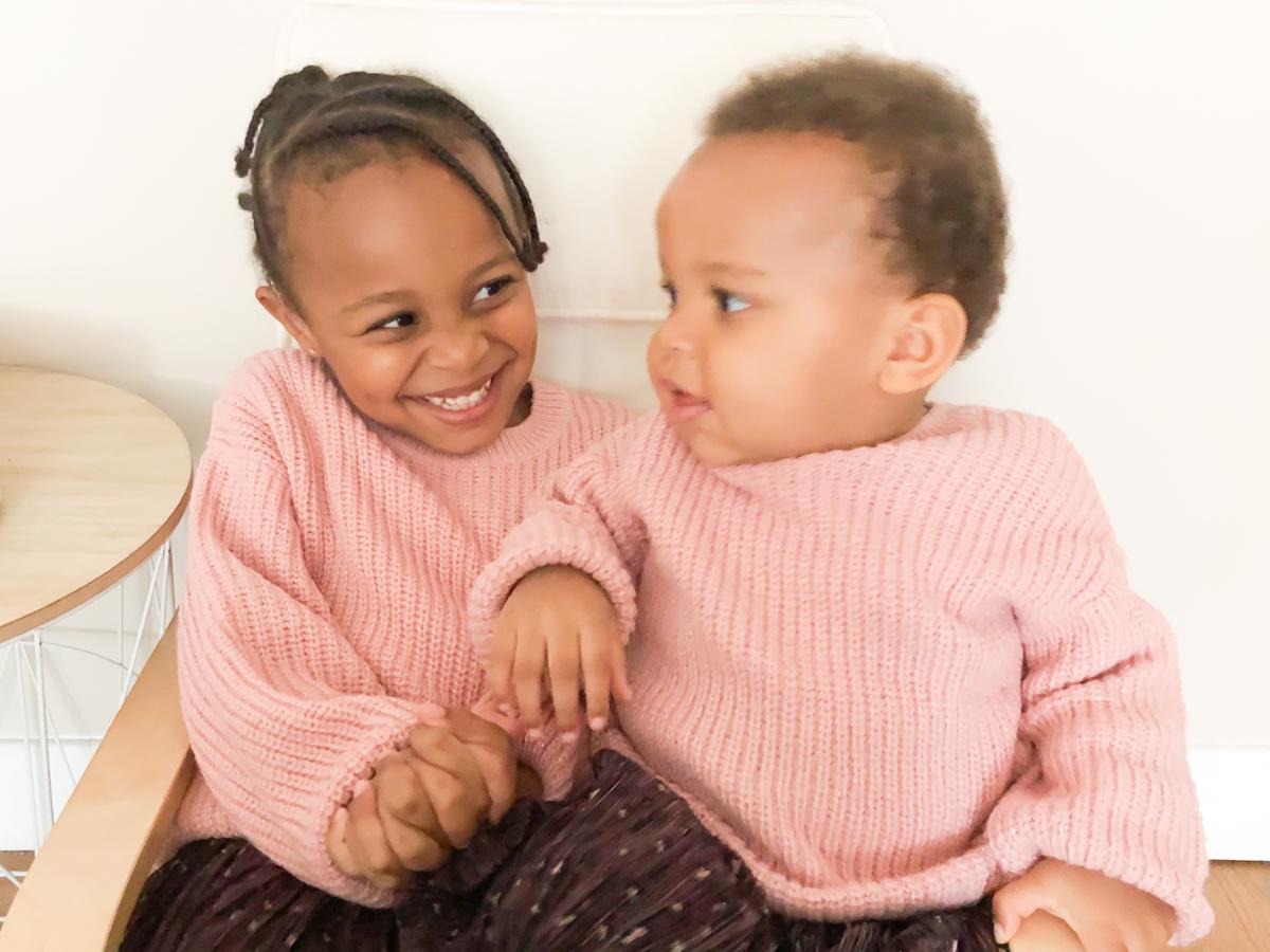 Deux petites filles complices assises sur un fauteuil